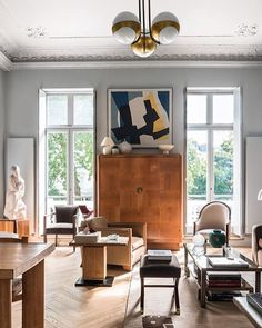A pair of French windows leads from the sitting room to the terrace with a painting by Rene Roche between them.  @houseandgardenuk