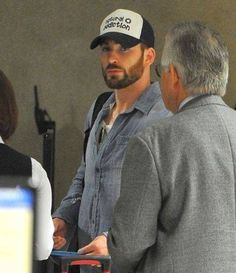 Chris Evans arrives at LAX Airport ahead of his departing flight out of Los Angeles. The 'Captain America' star dressed casual for his travels in a button up denim shirt, black jeans and a 'Natural Addiction' mesh hat.