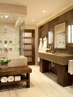 This relaxing bathroom combines natural wood with stone drainage beneath the sink and shower area. Rich dark woods and brick also make an appearance.
