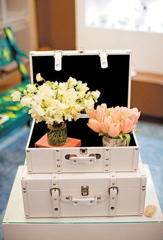 White and pink wedding centerpiece on a stack of vintage suitcases. Perfect for the Honeymoon money dance.