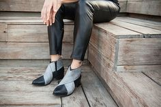 Black Leather Booties for women. Designer shoes for winter. A black and gray color combination.   Style name: River  These wonderful boots are uniquely designed in an X shape. They open at the inner side of the leg, using a zipper. This style has a 3 cm heel.  We only use the finest leather and a very comfortable shoe shape. However, we do not use leather soles, as they are more sensitive to wear and tear. We do use a soft manufactured durable sole so that you get the most wear possible out…