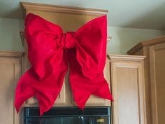 Giant holiday bows are all over Disney Parks during the holiday season. Here's a DIY tutorial that shows you how to make Giant Holiday Bows for your house.