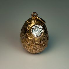A Solitaire Diamond and Gold Egg Pendant made in St. Petersburg between 1904 and 1908. The textured 14K gold egg is set with a sparkling old European cut diamond (approximately 0.30 ct). Marked with 56 zolotnik standard with initials of St. Petersburg assay master Alexander Romanov and maker's initials. Height without suspension ring – 16 mm (10/16 in.).