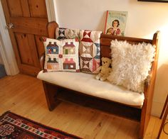 Spool quilt & House patchwork pillow displayed on a bench