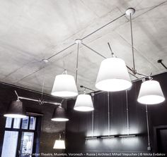 The mix of ecru and black diffusors for these #Tolomeo Basculante Suspensions is an unexpectedly good idea, boosted by those grey brick and concrete painted black walls. ► http://bit.ly/1YKB8ZC #Design Michele de Lucchi & Giancarlo Fassina