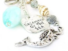 This mermaid keychain is nature inspired with its natural sea shells and silver fish charms. A seashell keychain that makes a sweet gift under 20.00. This quote keychain also is a great stocking stuffer or gift for her. There is an ocean colored stone and a mermaid charm to add extra beach inspiration. The square silver tone charm reads dreaming of the sea and makes a great small gift for any beach or ocean lover. CARRY THE SUMMER WITH YOU ALL YEAR LONG. This mermaid keychain measures 3.5…
