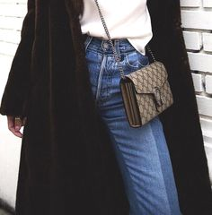 brown fur coat, white top, cross body Gucci bag and contrast jeans