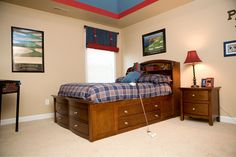 Navy plaid and red accents this teenage boys bedroom. Blue jean fabric stagecoach shades with red belt and buckles ties. Blue and red painted tray ceiling. Golf accessories and his name in large wooden letters.