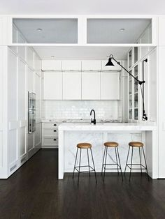 small kitchen seems very bright because of the white. black accents. Double height cabinets. Love the barstools.