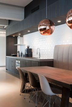 polished copper lighting against a black kitchen and warm wood table - Focus Brands © Remy Meijers