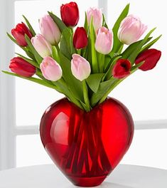 Season of Love ~ Employs blushing tulips to convey your heart's most ardent wishes on this coming Valentine's Day. Red and pink tulips are lovingly arranged in a designer red glass heart-shaped vase to create a flower bouquet like none other. Set to capture every season of your love, this flower arrangement will be the perfect way to celebrate this February 14th.
