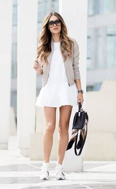 Wear the bomber jacket trend in beige over a white mini dress and with simple sneakers to steal Lydia Lise Millen's winning sporty chic style! Paired with shades and a leather bag, this look is perfect for summer! Dress: Zara, Jacket: ME EM, Trainers: Chanel, Scarf: Gucci, Bag: Louis Vuitton.