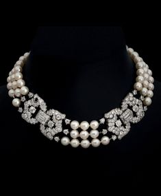CARTIER - An Art Deco three-strand cultured pearl necklace with two platinum and diamond plaques, circa 1920. Singed and numbered.