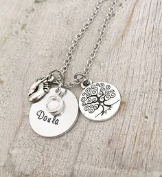 Doulas and Midwives help women have a safe, memorable, and empowering birthing experience and this is a perfect gift to show appreciation.  1- Solid Disc with the word Doula on a 3/4 disc (if you would like a different word that Doula please specify or I will assume you want Doula) 1- Tree of Life Charm 1- Babys Feet Charm 1- Swarovski Birthstone 1- Chain. 1.5mm Stainless Steel PLEASE SEE OTHER LISTING PICTURES FOR MORE EXAMPLES. If you would like to add a heart name tag please also purc...