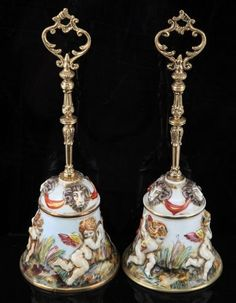 Bells decorated with cherubs along the sides and sheep at the top. Bells adorned with ornate gold colored handles. The bells including the handle stand at 12.25 inches high. Keramos R. Capodimonte maker mark inside both bells.