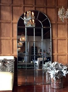 Chandelier reflections in this tall arch panelled window mirror