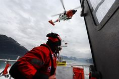 A Coast Guardsman tends the line of a hoist basket lowered by the aircrew of an MH-60 Jayhawk helicopter onboard the response boat-medium during rescue hoist training in Port Valdez, Alaska, Sept. 14, 2016. The helicopter crew is assigned to Coast Guard Forward Operating Location Cordova. Coast Guard photo by Petty Officer 1st Class Bill Colclough
