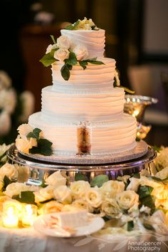 White wedding cake with a slice taken out. Classic Cheesecakes and Cakes bakery, Britt Wood Designs florist.