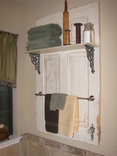 Fancy towel rack made from an old door cut in half vertically and hardware added to hang towels. Love this!
