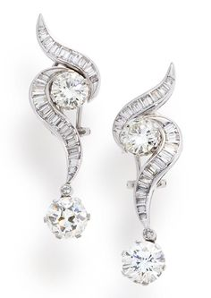 A pair of diamond pendant earrings  each designed as a baguette-cut diamond scroll, one accentuated by two round brilliant-cut diamonds, weighing 3.17 and 1.83 carats, the other accentuated by an old European-cut diamond, weighing 2.88 carats and a round brilliant-cut diamond, weighing 1.76 carats; remaining diamonds weighing approximately: 2.00 carats total; mounted in platinum; length: 2in.