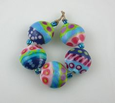 This is a fun, bold pastel set of 5 lentil shaped beads that are perfect for spring and summer! Each bead is embellished with dot and twisty stripe designs, in pink, purple, violet, lime green, turquoise and periwinkle. A lovely set, perfect for a necklace or bracelet. Each bead measures approx. 15 mm. diameter.