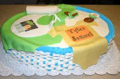 Boy baby shower basket cake; The blanket, onesie, bib, pacifier, rattle, and bottle are all made out of fondant.  The name on the onesie and the logo on the bib were made with an edible image printer.