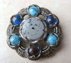 A Stunning large brooch manufactured under the trade name Miracle by A Hill and company Ltd.  The brooch is fashioned in a circular style with a large central faux marble stone and is surrounded by, six stones, three of faux turquoise and three of faux agate set in a silver tone metal. The setting has lovely Celtic style scroll work. Circa 1970's.  Signed Miracle faintly to the back of the brooch.
