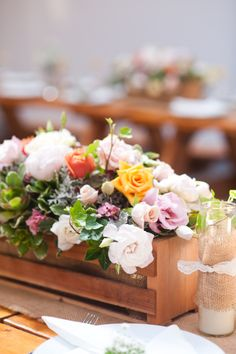 Rustic Western Wedding table flower arrangement in wooden box. Includes ivy, peonies, roses, succulents, and dusty miller foliage.