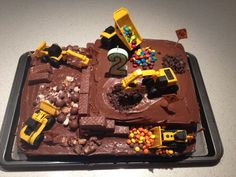 Construction themed birthday cake // Dump trucks // Diggers // toddler birthday cake - Made in Victoria, BC. Ingredients: mini m&m's, mini chocolate chips, malt balls (some crunched up), mini reese's pieces, reese sticks, mini construction set: https://www.amazon.ca/Toy-State-Caterpillar-Construction-Machine/dp/B003U0O3B4 , Toothpick construction signs from Amazon