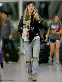 Multitasking: Cara Delevingne was making use of every minute as she chatted away to a friend on speaker phone as she made her way through the terminal at JFK Airport on Thursday