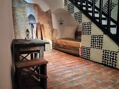 Unique experience in Seville/ Sevilla (Spain). Beautiful DIY rustic sitting area under stairs with DIY handmade rustic wood couch with burlap cushions. Decorated with bale hay, farmers tools like shovel and ceramic/ crystal/ glass oil lamp for lightning. Located in a DIY rustic home/ house with distressed stone brick wall, DIY stone flooring and handmade wood furniture with a splash of Arabic style and pattern. Located in South Spain. Ideas, design and more info on juancarloscoquerel.com