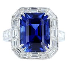 Vivid 6.81ct Emerald Cut Sapphire & Diamond Ring/ Platinum solitiare ring consisting of 1 emerald cut sapphire weighing 6.81 carat set with 1.96 carats total weight of baguette and asscher cut diamonds.