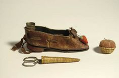 "Sister's shoe sewing kit, leather shoe lined with fabric, brown silk ribbon, includes thimble and thimble case, basketry scissors case with scissors, red strawberry emery, and miniature basket with velvet tomato pincushion, Canterbury, NH, heel lifts up to expose fabric needleholder, 5"" l, (purchased from Doug Hamel). Willis Henry Auctions"