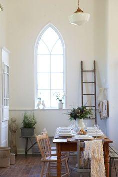 Gothic arched window, farmhouse table, schoolhouse light fixture.