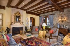 French Normandy Home - Living Room; French Country Style Fabrics and Decorative Pieces Are Throughout The Home. Notice all of he stone, that is a predominant feature in French Normandy architecture