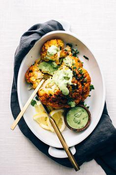Tandoori Cauliflower Roast with Garlic-Cilantro Yogurt Sauce | Cauliflower is coated in tandoori-spiced vegan sauce + roasted until tender and golden!