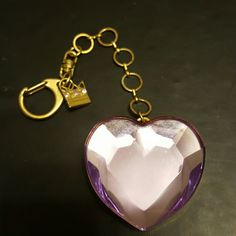 Vera Wang Heart Keychain A gold colored chained Vera Wang keychain with a big purple looking diamond heart. The heart slides open and has a small place to store things. A small gold crown is an accent on the chain. Heart charm is about 2-2.5 inches long, chain about 3-4 inches. Vera Wang Other