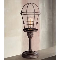 With its rounded, caged shade and slender base, this small industrial accent lamp charmingly mimics the silhouette of a light bulb.