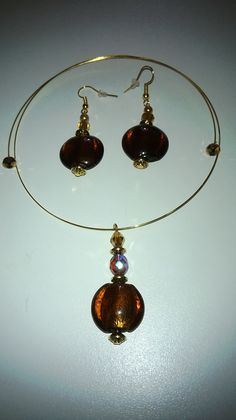 Brandy coloured glass beads used to adorn earrings and a choker. Gold beads on the ends of the choker to avoid accidents and impailments.