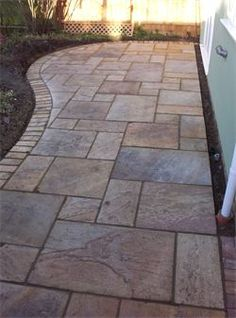 Natural Indian sandstone paving patio with curved brick edge.