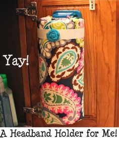 This is genius!!  So doing this very soon!---a paper towel holder, fabric covered roll of paper towels=headband/clip holder for bathroom cabinet!  Love it!