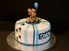 Moose themed birthday cake with a fondant and gumpaste moose holding a balloon and moose tracks down the side.