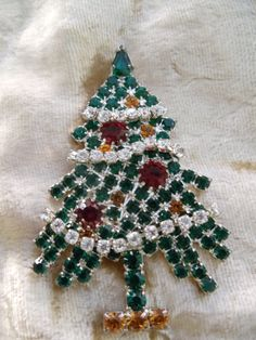 The Christmas tree is green rhinestones, with white garland going around and red and yellow rhinestones as decorations on the tree. Description from etsy.com. I searched for this on bing.com/images