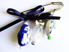 Broche métallique avec des perles fimo bleu, blanc, vert fait main, et un nœud papillon bleu. La broche fait 5,5 de long et environ 3 cm en suspension. Elle est prévue pour être accrochée aux tissus rigides, comme sacs, manteaux, vestes, autres accessoires, pulls en maille rigide, lâche car l'aiguille est très forte! Fait main!