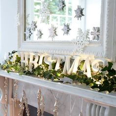 """use old windows and white """"christmas"""" on green garland with white accessories and stockings"""