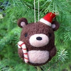 Add a little cuteness to your Christmas tree with this adorable needle felted bear ornament. He comes wearing a Santa hat and holding a tiny candy cane and is handmade with love out of natural wool.