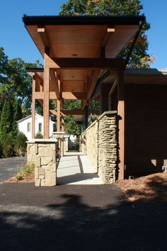 Morris Builders, Inc. gave this outdated, mid-century modern dentist office a craftsman style face life with exposed cedar timbers, a handicapped accessible ramp and a pop of color. exterior - office - dentist - medical - ramp - accessible - handicapped - stone - blue - grey - gray - white - steel - exposed - roof - truss - cedar - beam - column - window - mid century modern - craftsman - face lift - remodel - construction - modern - industrial - entrance - entry