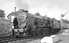 A grand old 'Lord Nelson' 4-6-0 waits at New Milton with a down London to Bournemouth semi-fast. The whole class were named after famous British maritime heros. New Milton, Hampshire, England. Negative scan.
