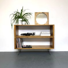 This is a double height storage cabinet designed to store extra large volumes of vinyl records. It can also be used as a sideboard, console or bookshelf.  It is hand made from high quality softwood timber and is fitted with sturdy Eames style hairpin legs for a minimalist, natural Nordic chic look. This unit is fine sanded, stained and sealed with an oil stain and a low-sheen, natural look, hardwearing finish in a choice of colour options. This size will fit around 640 vinyl records if fully…
