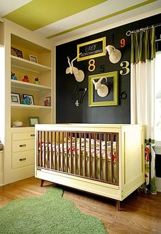 Bold green stripes on the ceiling of this beautiful nursery. On the wall are the numbers 1-9 joined by felt taxidermy.